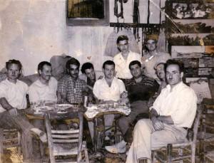 Στο καφενείο του Χρήστου Σκούρα. Από δεξιά: Χρήστος Σκούρας, Χαράλαμπος Κόκλας, Γιώργος Δούνας, Γιάννης Σιμιτζής, Δημήτρης Σιμιτζής, Νικόλαος Δούνας, Δημήτρης Παλαιολόγος, Γιαννης Βασιλίου Σιμιτζής και πάνω Ηλίας Σκούρας και Χρήστος Λεμπέσης